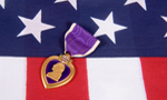 A Purple Heart, a medal awarded to U.S. military personnel wounded or killed in action, is placed on an American flag